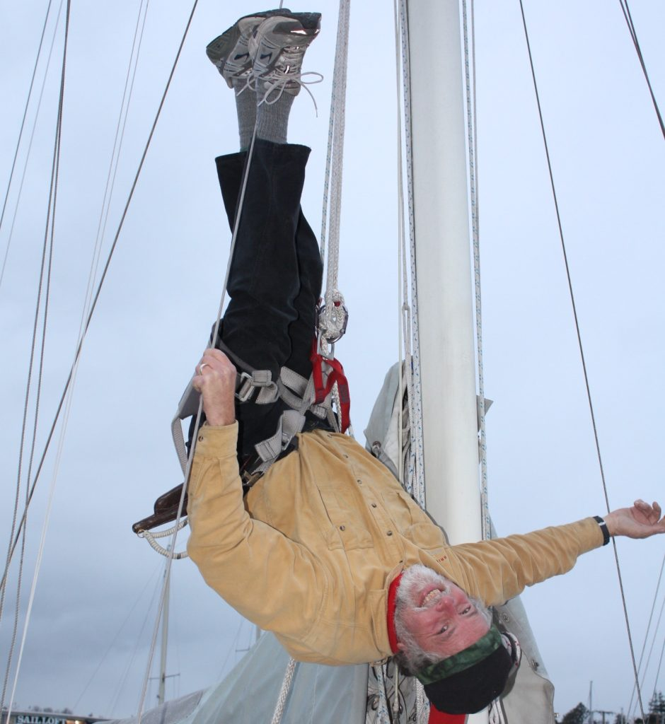 Brion Toss hanging upside down in a harness from a sailboat mast.